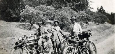 Three men standing beside old motorcycles on dirt road in the 1950s.