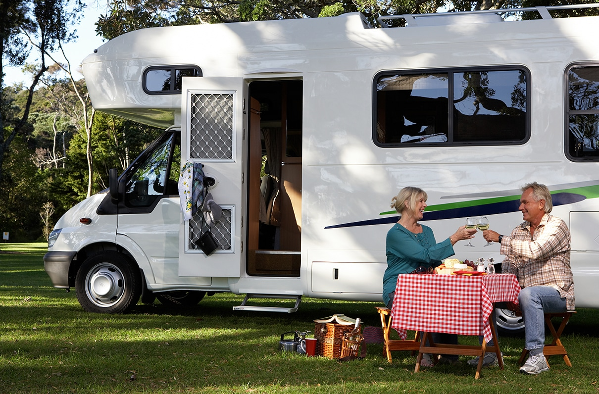 Two RV travelers toasting at their campsite with wine.