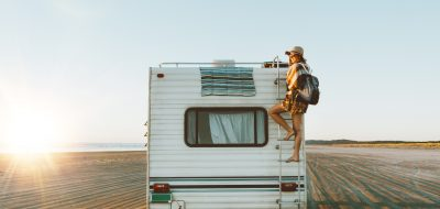Young woman climbing ladder on motorhome on beach