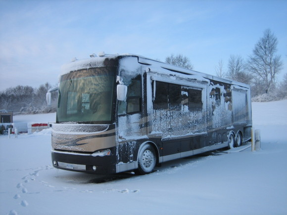 Large brown and tan RV in snowy weather