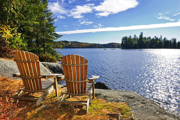 A pair of Adirondack chairs overlook a lake.
