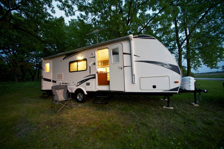 White travel trailer with door open parked on grass and dirt at dusk