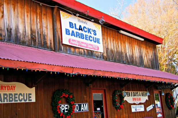 Wooden building showing Black's Barbecue sign and red awning with Christmas decorations