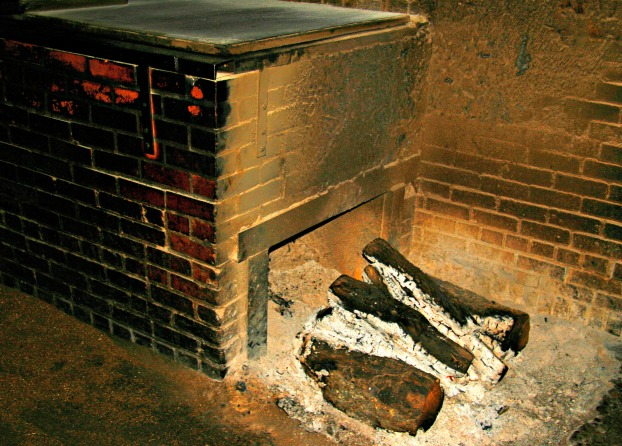 Brick oven showing charred logs of wood and ash