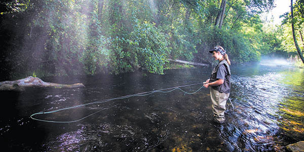 A woman wearing waders smiles as she fly fishes in a stream.