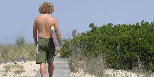Curly-haired guy in bathing suit totes a boogie board along a wooden walkway toward the beach.