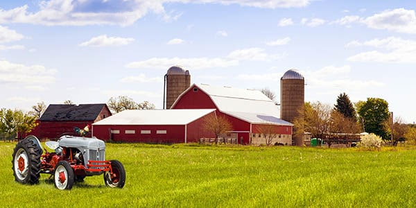 A tractor in the foreground, red barn and brown silos in background.