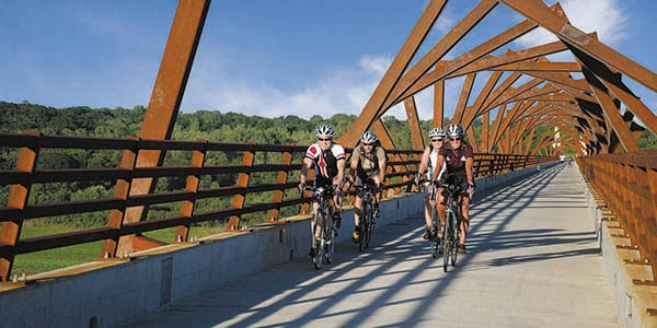 Four cyclists with helmets ride on a bridge with an interesting canopy.