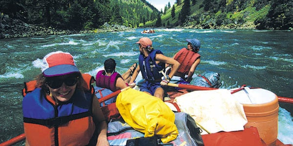 Four rafters wearing life vests approach a series of rapids in a river valley.