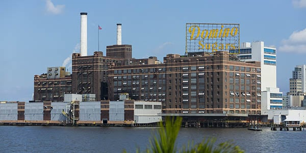 A large factory with the sign, Domino Sugar, sits on a waterfront.