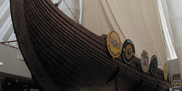 A viking ship with round shields mounted on its side.