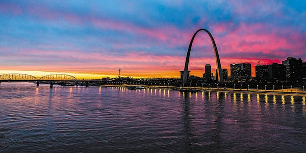 The graceful St. Louis Arch reflected on the vast Mississippi