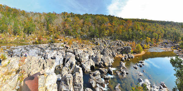 Rugged rock bluff looms over a calm clear pond in the Ozarks