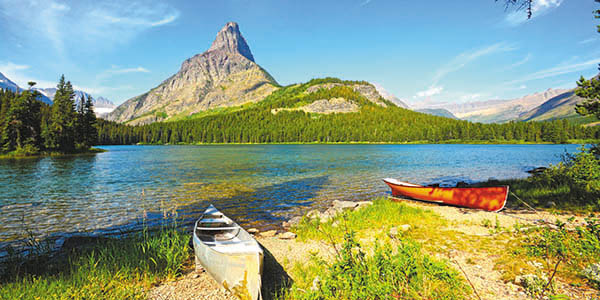 Two canoes rest on the banks of a lake with a mountain in the background.