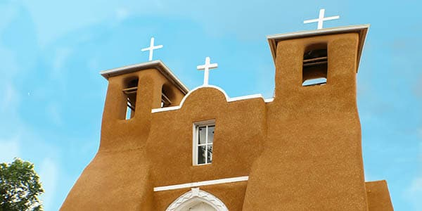 A brown adobe church stands against a clear blue sky.