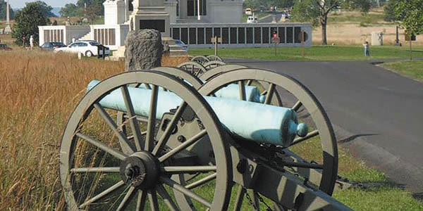 A Civil War-era cannon on a roadside that leads to a monument.