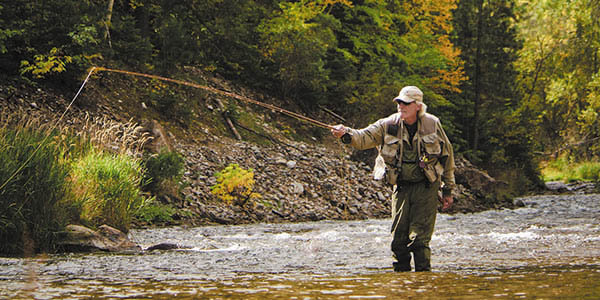 A fly fisherman casts a line down the stream.