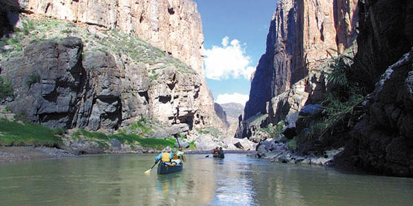 Paddlers in a canoe enter a narrow stretch of river bordered by high, sheer rock walls.