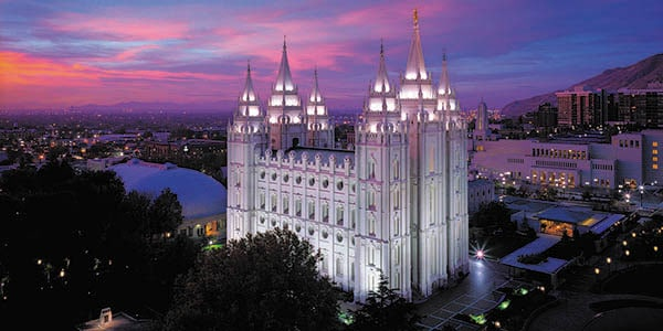 The Mormon Temple with six spires illuminated in the midst of a city.