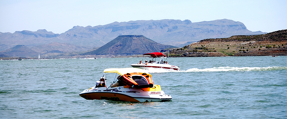 A speedboat in a lake surrounded by rugged mountains and hills.