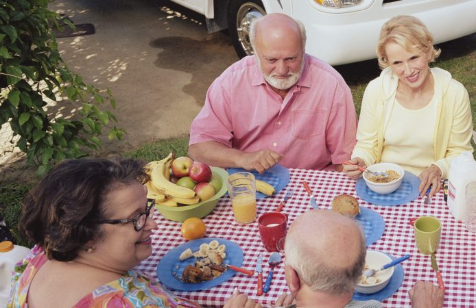 Two senior couples eating breakfast outdoors