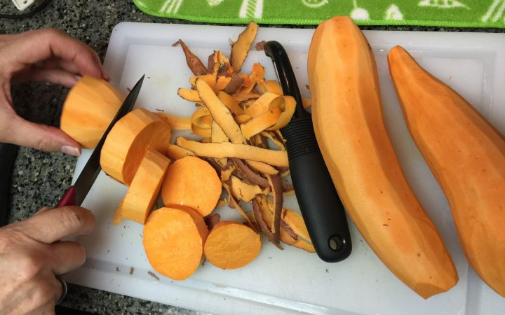Person cutting and peeling yams on plate
