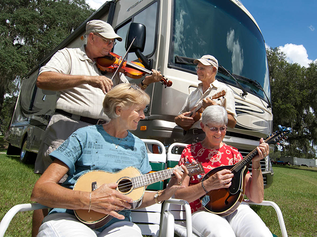Two elderly couples playing violin, banjo and guitar next to motorhome, outside