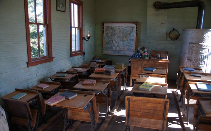 Old classroom with wooden desks and books on top