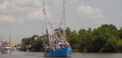 Blue shrimp boat with colorful flags on mast in Iberia Parish, Louisiana