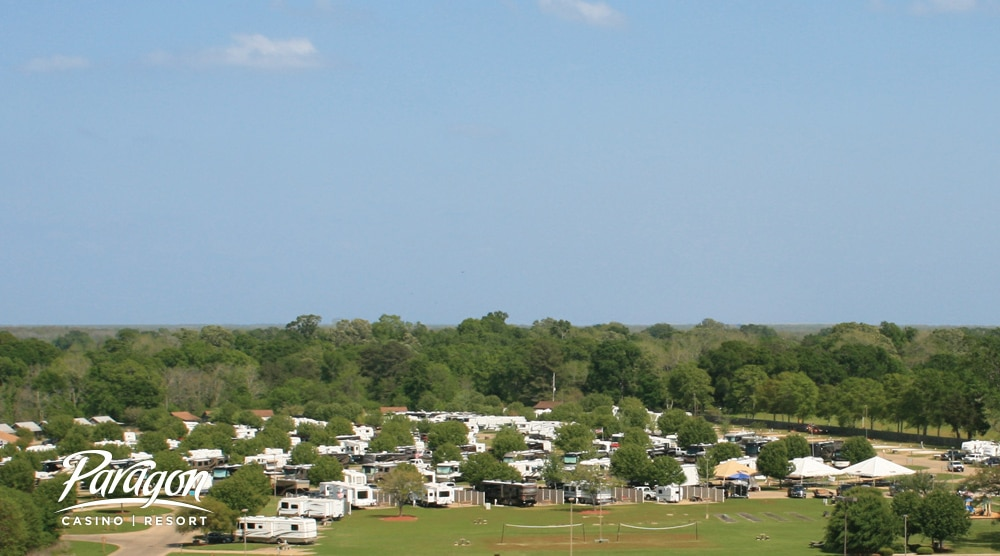 Aerial view of many RVs and Trailers camped at resort with lush greens in background