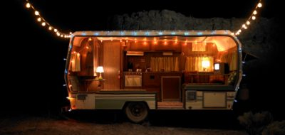 Travel trailer decorated in holiday lights at night