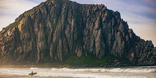 Morro Rock dwarfs a surfer on the shore.