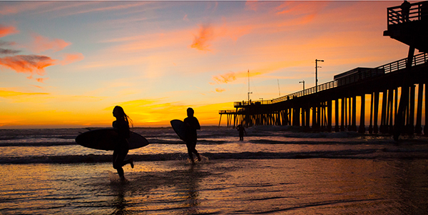 Couple with surf boards at sunset.