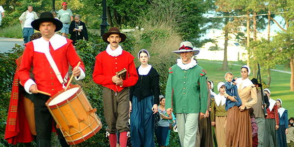 Costumed reenactors parade through Plymouth.
