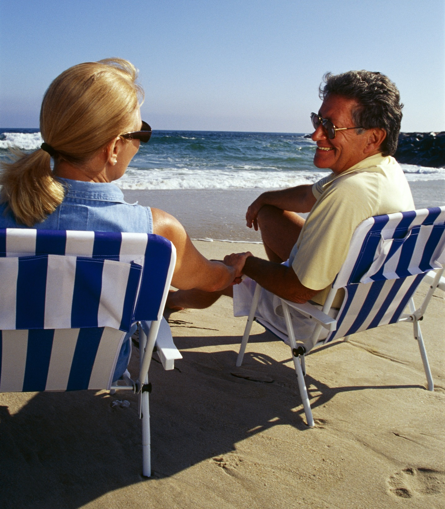 Blonde haired woman and tan older man holding hands sitting on beach chairs