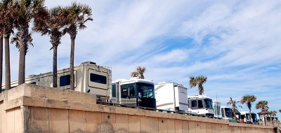 Four motorhomes parked against beach concrete wall