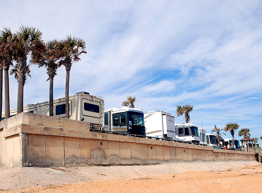 Several motorhomes parked against beach concrete wall