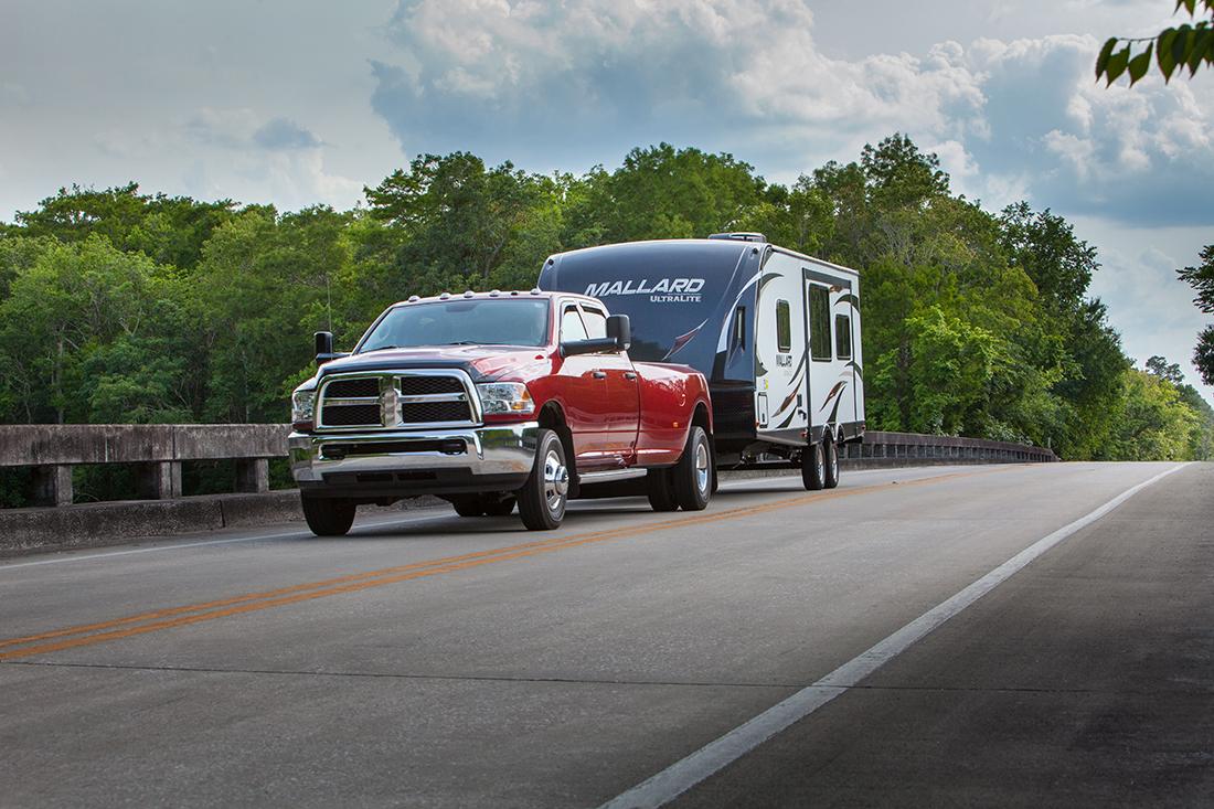 Red truck pulling Mallard travel trailer down two lane road