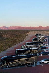 Drone shot of RVs parked in a row in a desert RV park.