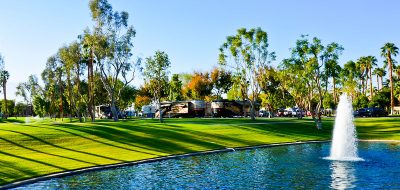 Palm Desert golf course at RV resort tree shadows on green grass next to water