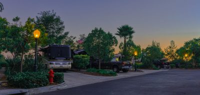 Large motorhome parked in driveway with green trees at dusk