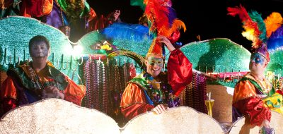 Dancers and performers wearing Mardi Gras colorful clothes