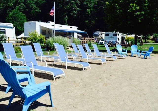 Riverdale Farm Campsite - lounge chairs by swimming pond