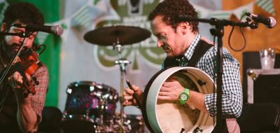 Man playing large handheld drum on stage, with drum set in background
