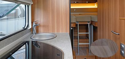 RV kitchen area with small sink and wood paneling
