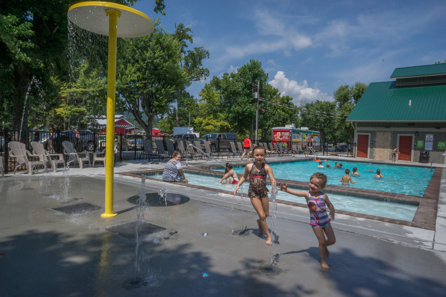 Kids running and smiling around pool on sunny day