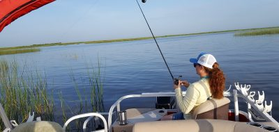 Woman wearing baseball hat fishing from back of boat on sunny day