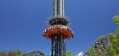 Ride at theme park with tall ride and circular seating area around it with people in seats