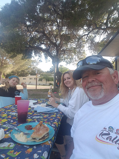 Family smiling and eating outside while camping