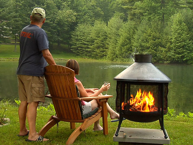 Couple gazing at lake next to fire pit